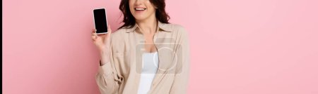 Photo for Panoramic shot of smiling woman showing smartphone with blank screen on pink background - Royalty Free Image