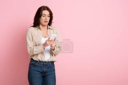 Photo pour Belle femme brune utilisant un smartphone sur fond rose, concept de corps positif - image libre de droit