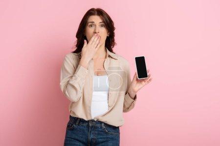 Photo pour Femme choquée couvrant la bouche avec la main et montrant smartphone sur fond rose, concept de corps positif - image libre de droit