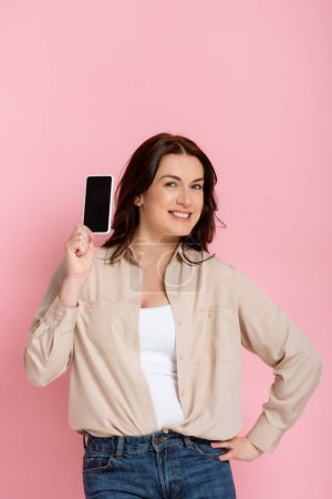 Photo for Beautiful smiling woman with hand on hip showing smartphone with blank screen isolated on pink - Royalty Free Image
