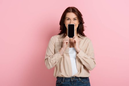 Photo pour Femme brune montrant smartphone avec écran vide près du visage sur fond rose - image libre de droit