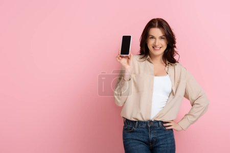 Photo for Beautiful woman smiling at camera while showing smartphone with blank screen on pink background - Royalty Free Image