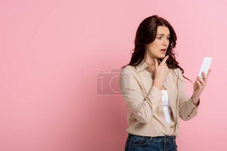 Photo pour Femme inquiète pointant du doigt tout en utilisant un smartphone sur fond rose - image libre de droit