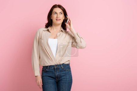 Photo for Attractive brunette woman looking away while talking on cellphone on pink background - Royalty Free Image