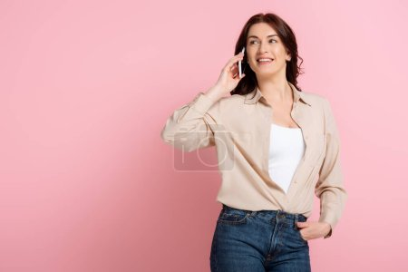 Photo for Positive woman smiling while talking on smartphone on pink background, concept of body positive - Royalty Free Image