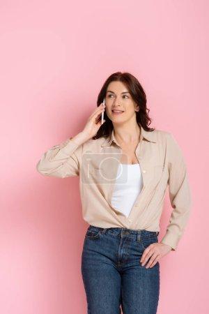 Photo pour Attrayant brunette femme souriant tout en parlant sur smartphone sur fond rose, concept de corps positif - image libre de droit