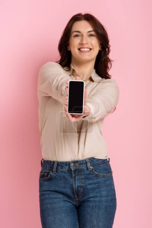 Photo for Selective focus of beautiful brunette woman showing smartphone on pink background - Royalty Free Image