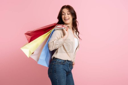 Photo for Positive woman smiling while looking at shopping bags isolated on pink, concept of body positive - Royalty Free Image