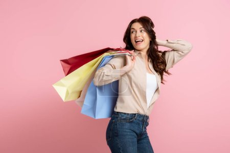 Photo for Cheerful brunette woman with hand near head holding colorful shopping bags on pink background - Royalty Free Image