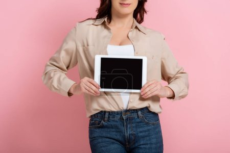 Photo for Cropped view of woman holding digital tablet on pink background, concept of body positive - Royalty Free Image