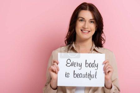 Foto de Hermosa mujer sonriente sosteniendo la tarjeta con cada cuerpo es hermoso letras sobre fondo rosa - Imagen libre de derechos