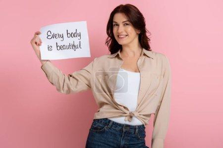 Foto de Atractiva morena mujer con tarjeta de celebración con cada cuerpo es hermoso letras sobre fondo rosa - Imagen libre de derechos