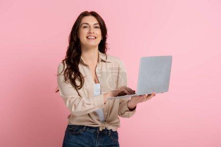 Photo pour Brunette femme souriant à la caméra et en utilisant un ordinateur portable sur fond rose - image libre de droit
