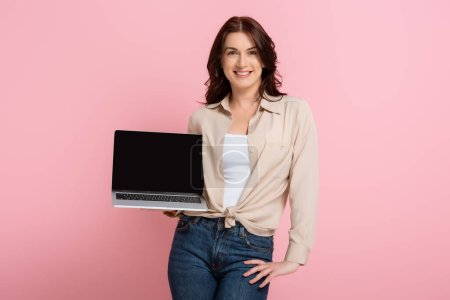 Photo for Attractive smiling woman with hand on hip showing laptop isolated on pink, concept of body positive - Royalty Free Image