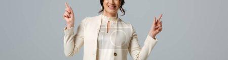 Foto de Imagen horizontal de una mujer de negocios sonriente señalando con los dedos aislados en gris - Imagen libre de derechos
