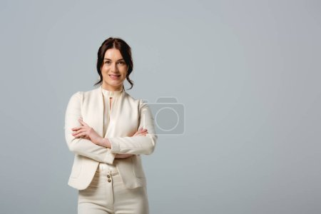 Photo for Beautiful businesswoman with crossed arms smiling at camera isolated on grey, concept of body positive - Royalty Free Image