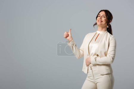 Photo for Beautiful smiling businesswoman showing thumb up isolated on grey - Royalty Free Image