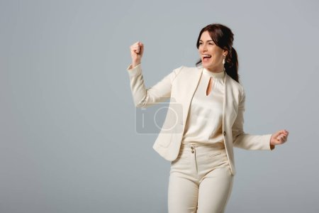 Photo for Positive businesswoman showing yeah gesture isolated on grey, concept of body positive - Royalty Free Image