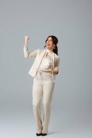 Photo pour Femme d'affaires heureuse montrant geste ouais sur fond gris - image libre de droit