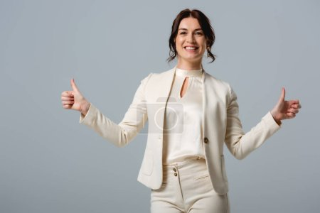 Photo for Beautiful smiling businesswoman showing thumbs up and looking at camera isolated on grey - Royalty Free Image