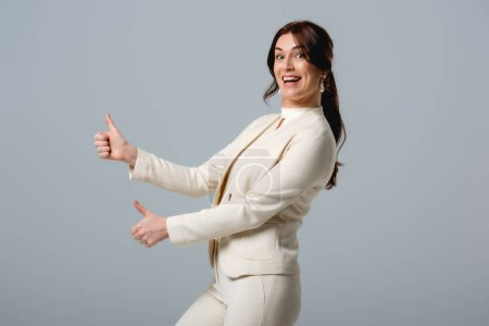 Photo for Side view of beautiful smiling businesswoman showing thumbs up isolated on grey - Royalty Free Image
