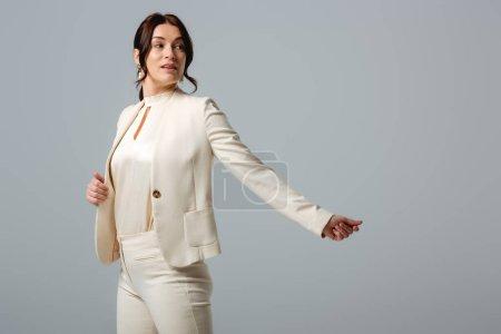 Foto de Hermosa mujer de negocios mirando hacia otro lado aislado en gris, concepto de positividad corporal - Imagen libre de derechos