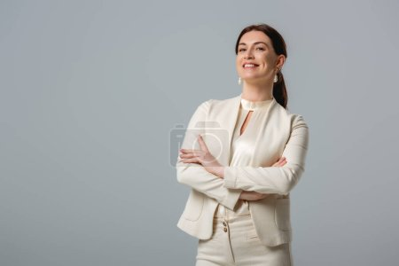 Photo for Attractive smiling businesswoman with crossed arms looking at camera isolated on grey - Royalty Free Image
