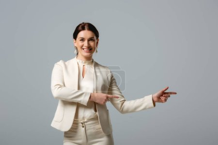 Smiling woman in formal wear pointing with fingers isolated on grey