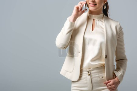 Photo for Cropped view of smiling businesswoman talking on smartphone isolated on grey - Royalty Free Image