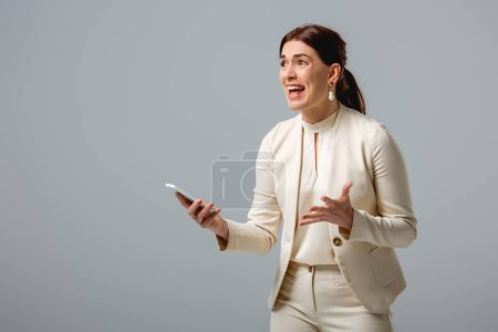 Angry businesswoman holding smartphone isolated on grey, concept of body positive