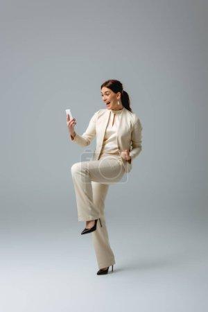 Photo pour Femme gaie en tenue formelle montrant un geste oui lors de l'utilisation du smartphone sur fond gris - image libre de droit