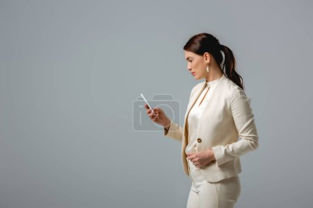 Photo pour Vue latérale d'une femme d'affaires attrayante utilisant un smartphone isolé sur gris - image libre de droit