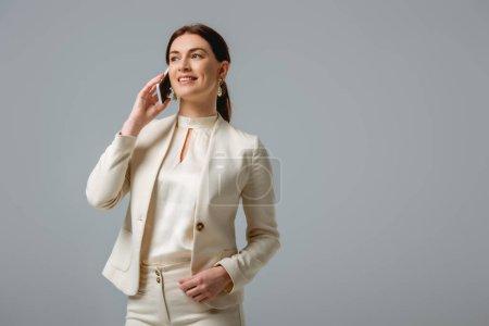 Photo pour Attrayant femme en tenue formelle souriant tout en parlant sur smartphone isolé sur gris - image libre de droit