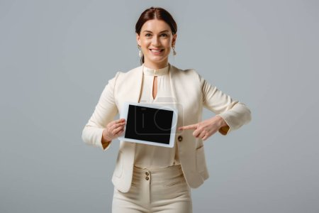 Beautiful smiling businesswoman pointing with finger at digital tablet isolated on grey