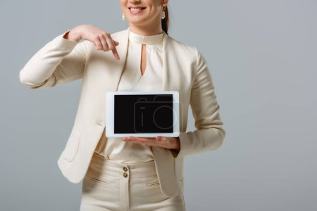 Photo for Cropped view of smiling businesswoman pointing at digital tablet isolated on grey - Royalty Free Image
