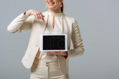 Photo pour Vue recadrée d'une femme d'affaires souriante pointant vers une tablette numérique isolée sur gris - image libre de droit