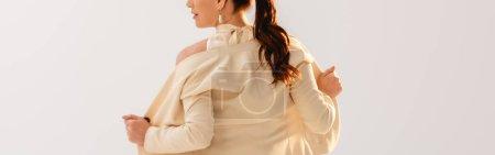 Foto de Orientación panorámica de la empresaria morena quitándose la chaqueta aislada en gris - Imagen libre de derechos