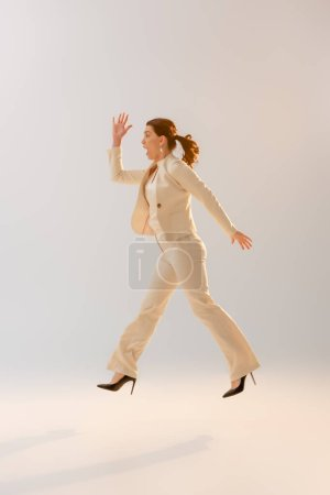 Photo for Side view of woman in formal wear jumping on grey background - Royalty Free Image