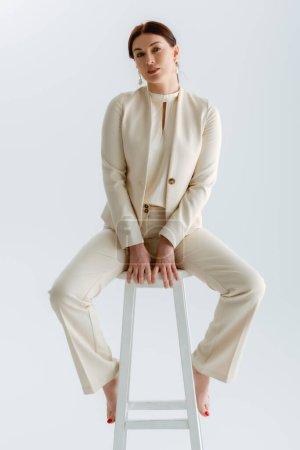 Photo pour Belle femme d'affaires pieds nus en tenue formelle regardant la caméra tout en étant assis sur une chaise isolée sur gris - image libre de droit