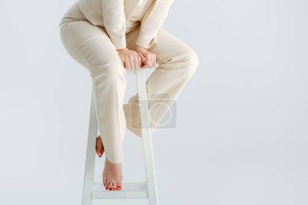 Photo pour Vue recadrée d'une femme pieds nus en tenue de cérémonie assise sur une chaise isolée sur du gris, concept de corps positif - image libre de droit