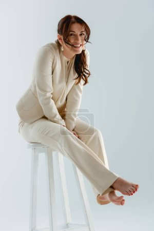 Photo for Cheerful barefoot businesswoman smiling at camera while sitting on chair isolated on grey, concept of body positive - Royalty Free Image