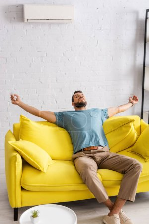 Young man holding remote controller of air conditioner while sitting with closed eyes on sofa at home