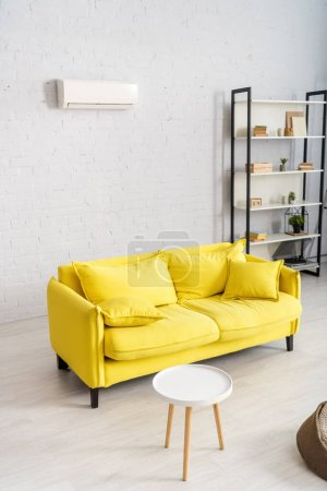 Interior of living room with yellow couch and air conditioner on wall