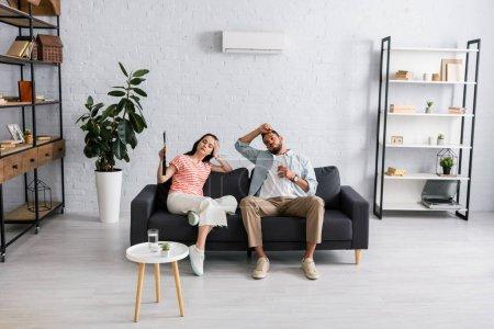 Junge Frau hält Ventilator neben Freund mit Glas Wasser, während sie zu Hause unter Hitze leidet
