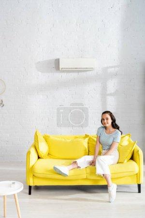 Photo for Young woman smiling at camera while sitting on sofa near remote controller of air conditioner on coffee table - Royalty Free Image