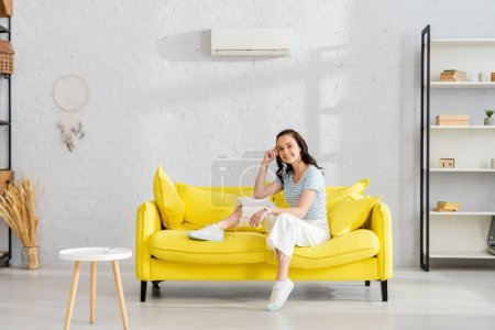 Photo for Beautiful woman smiling at camera while sitting on sofa in living room - Royalty Free Image