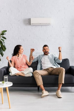 Photo for Smiling couple showing yes gesture while sitting under air conditioner on sofa - Royalty Free Image