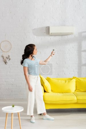 Young woman switching air conditioner with remote controller in living room