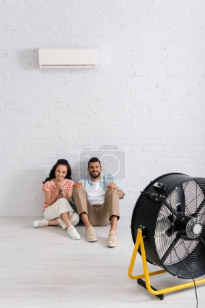 Photo for Positive couple sitting on floor under air conditioner and electric fan - Royalty Free Image