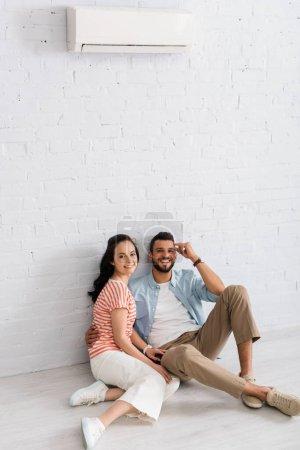 Homme barbu embrassant petite amie tout en étant assis sur le sol près du climatiseur sur le mur à la maison